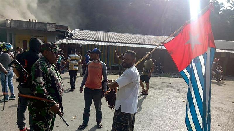 A protester carries the banned 'morning star' Papuan flag as he faces an Indonesian soldier in the city of Fakfak [Str/AFP]