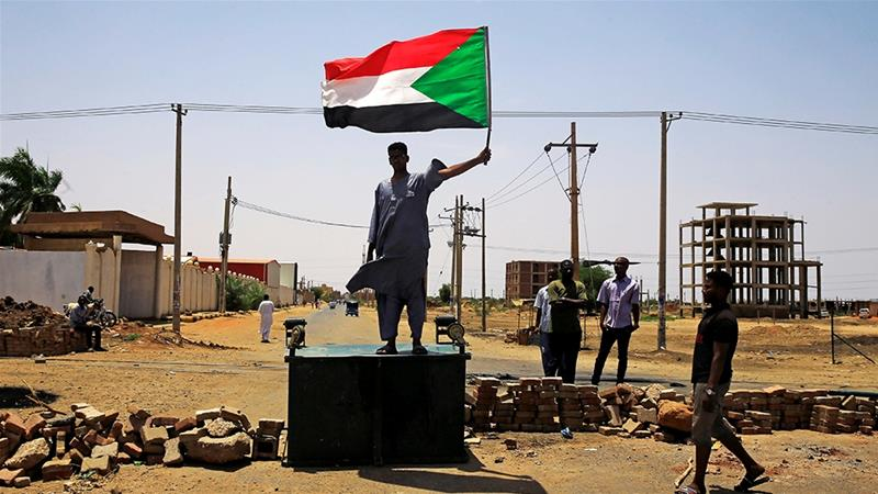 A Sudanese protester holds a national flag as he stands on a barricade along a street in June, 2019 [File: Reuters]