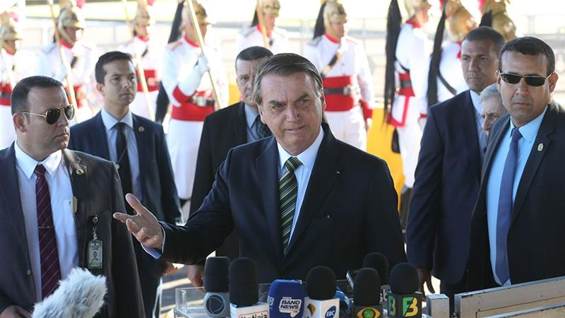 In this handout photo released by the government news agency Agencia Brasil, Brazil's President Jair Bolsonaro, speaks to the reporters outside the presidential official residence Alvorada Palace, in Brasilia, Brazil [Handout/Antonio Cruz/Agencia Brasil/AP Photo]