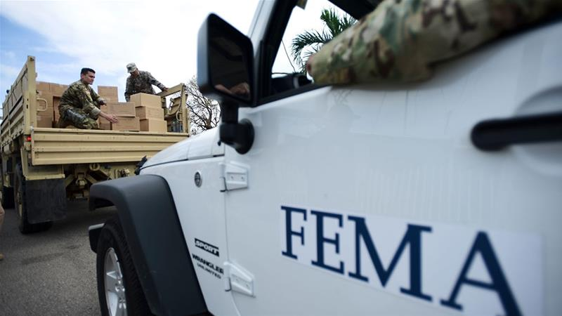 Department of Homeland Security personnel deliver supplies to Santa Ana community residents in the aftermath of Hurricane Maria in Guayama, Puerto Rico [File: Carlos Giusti/AP]