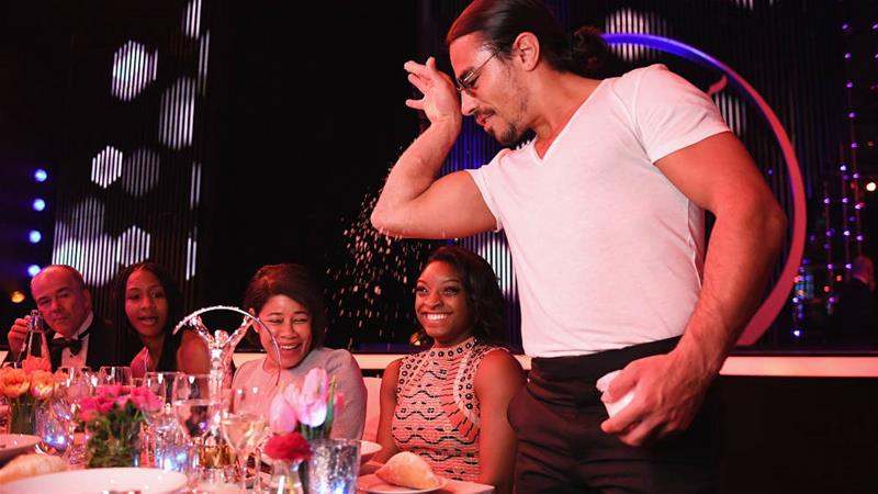 Nusret Gokce, known as 'Salt Bae', adds salt to the meal of gymnast Simone Biles of the USA [Stuart C. Wilson/Getty Images for Laureus]