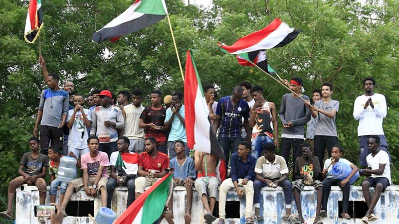 Sudanese demonstrators wave their national flag as they celebrate in Khartoum after protest leaders and the military agree on a constitutional declaration [Ebrahim Hamid/ AFP]