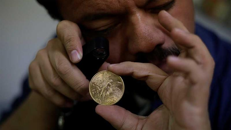 The owner of an antiques shop checks a Mexican gold coin, or centenario -  the same type of coin that was recently stolen [File: Jose Luis Gonzalez/Reuters]
