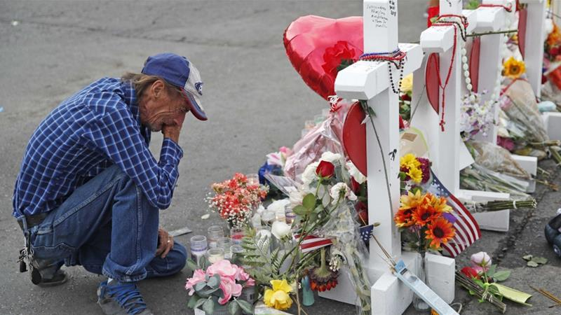 A man cries beside a cross at a makeshift memorial near the scene of an August 3 mass shooting at a shopping complex on August 6, 2019 in El Paso, Texas [AP Photo/John Locher]