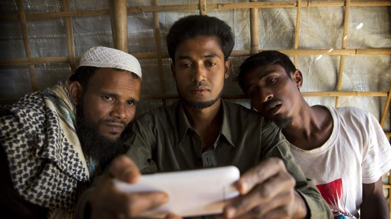 Rohingya refugee Mohammad Karim, 26, centre, shows a mobile video of Gu Dar Pyin's massacre to other refugees in Kutupalong refugee camp, Bangladesh [File: Manish Swarup/AP]