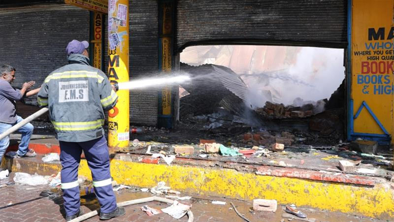 A shopkeeper watches as a fireman douses a burned and damaged property after overnight unrest and looting in Johannesburg [Marius Bosch/Reuters]