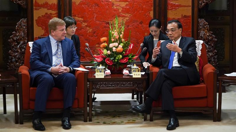 Chinese Premier Li Keqiang talks with Executive Vice President and Head of International Affairs at the US Chamber of Commerce Myron Brilliant, during a meeting with a group of American entrepreneurs in Beijing [Andrea Verdelli/Pool/Reuters]