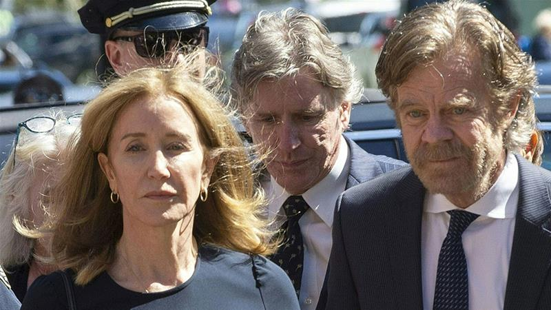 Actress Felicity Huffman, escorted by her husband William H Macy, makes her way to the entrance of the John Joseph Moakley United States court [Joseph Prezioso/AFP]