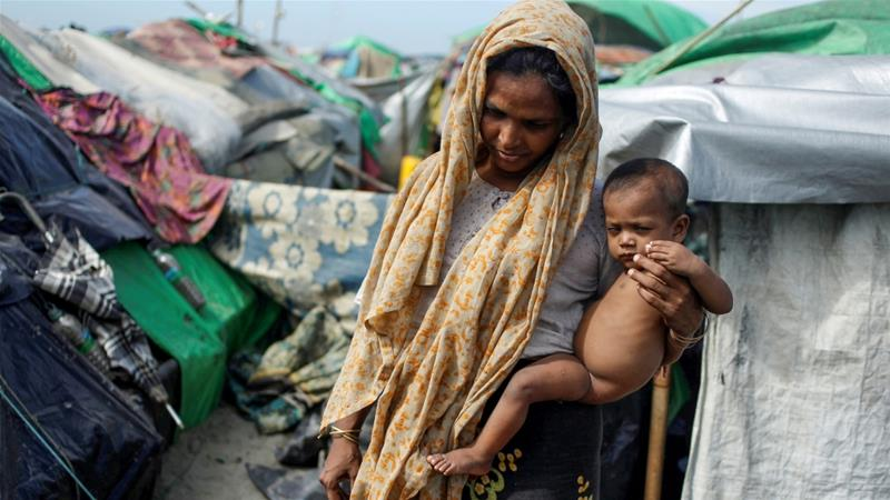 A Rohingya Muslim holds her baby as they wait to cross the border to go to Bangladesh, in a temporary camp outside Maungdaw, northern Rakhine state [Reuters]