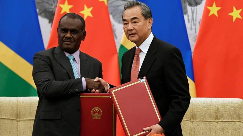 Jeremiah Manele, left, and Wang Yi, right, signed an agreement to establish diplomatic ties [Naohiko Hatta/Pool via Reuters]
