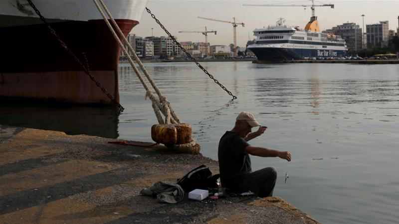 A man fishes at the port of Piraeus as passenger ferries are moored during a 24-hour strike in Greece [Costas Baltas/Reuters]