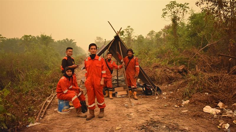 Volunteers, often poorly equipped, are tackling enormous blazes that have sent toxic smog across Southeast Asia. These men usually work as security guards for a plantation company but have spent two months fighting the fires [Raymondo/Al Jazeera]