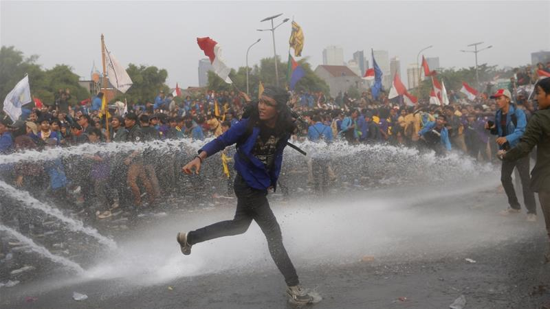 Student protesters are drenched by police water cannon trucks during anti-corruption protests outside the parliament in Jakarta on Tuesday. Dozens were injured in the violence. [Tatan Syuflana/AP Photo]