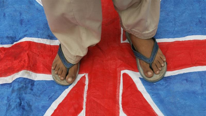 A demonstrator stands on a British flag during an anti-Israel rally in Karachi July 21, 2006 [File: Zahid Hussein/Reuters]