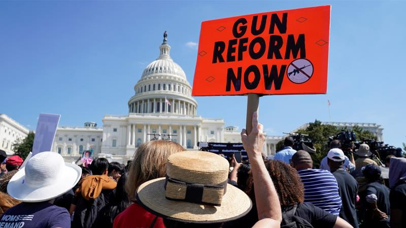 A protester holds up a sign during a demonstration calling for Congress to pass gun safety laws at the US Capitol in Washington, DC, September 25, 2019 [Kevin Lamarque/Reuters]