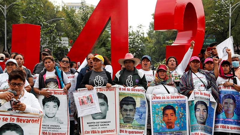 People hold up posters during a march to mark the fifth year since the disappearance of the 43 students of the Ayotzinapa Teacher Training College in the state of Guerrero [Carlos Jasso/Reuters]