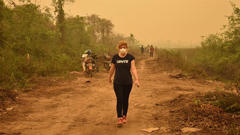 Aisyah Llewellyn reporting from Jambi, wearing an N95 mask, which filters out potentially dangerous particulate matter, but makes it difficult to interview people. [Raymondo/Al Jazeera]