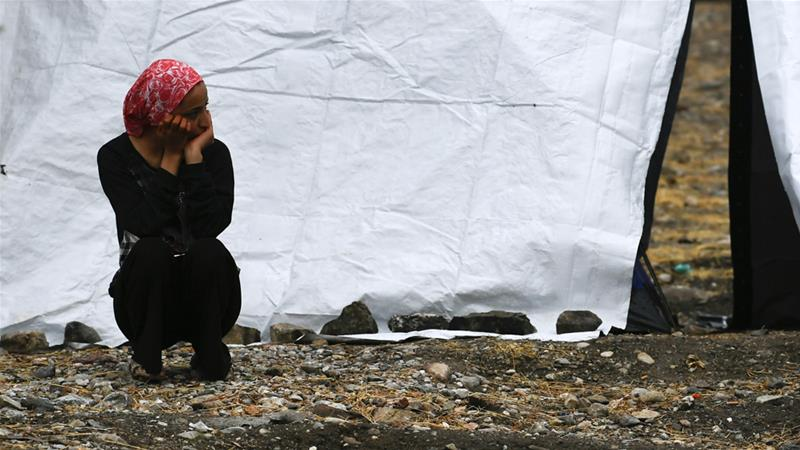 A woman sits outside a tent after a rainstorm near the Moria refugee camp [Michael Varaklas/AP]