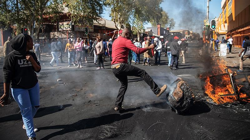 A man kicks a burning piece of furniture during a riot in the Johannesburg suburb of Turffontein on September 2, 2019 [Michele Spatari/AFP]
