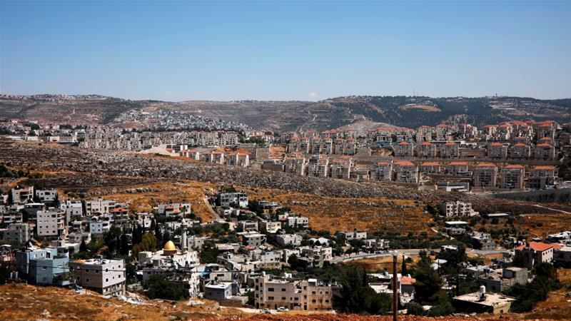 A general view shows Palestinian houses in the village of Wadi Fukin as the Israeli settlement of Beitar Illit is seen in the background, in the occupied West Bank [File: Nir Elias/Reuters]