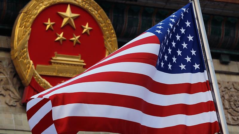 An American flag is flown next to the Chinese national emblem [File: Andy Wong/AP Photo]