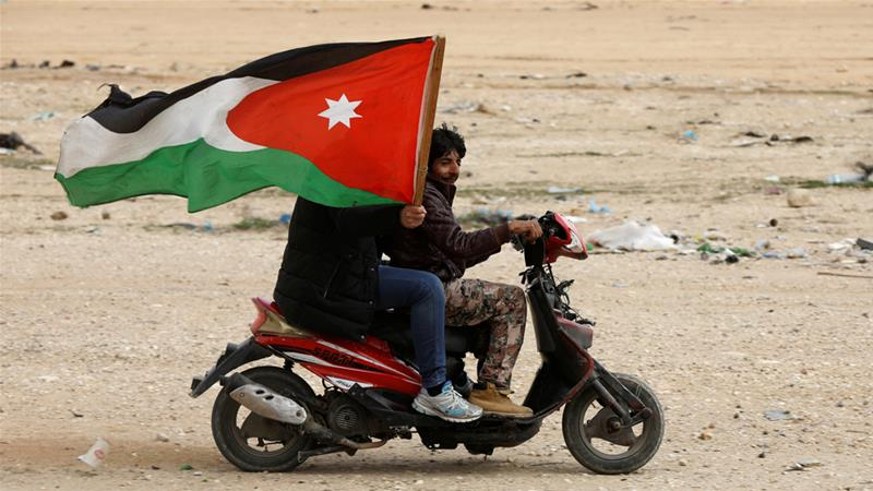 A man holds a Jordanian flag during a march demanding more employment opportunities near Amman in February [Muhammad Hamed/Reuters]