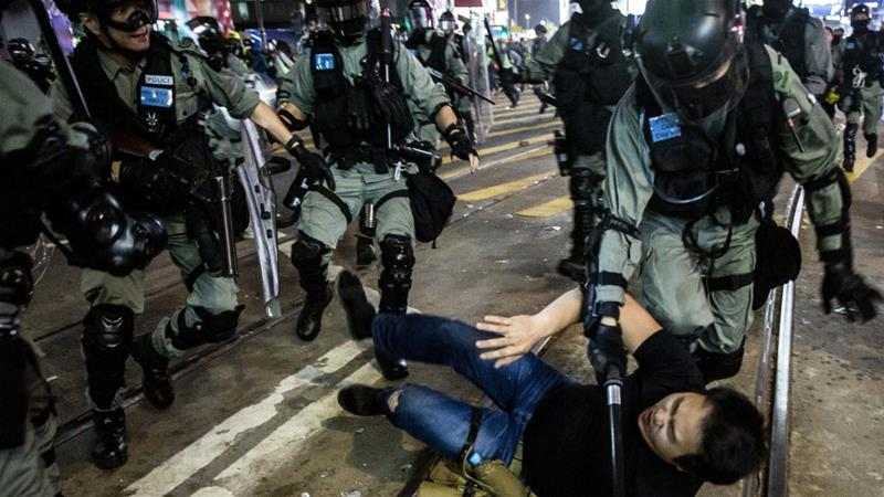 Police detain a man after a 'pro-democracy' march in Hong Kong on January 1, 2020 [Isaac Lawrence/AFP]
