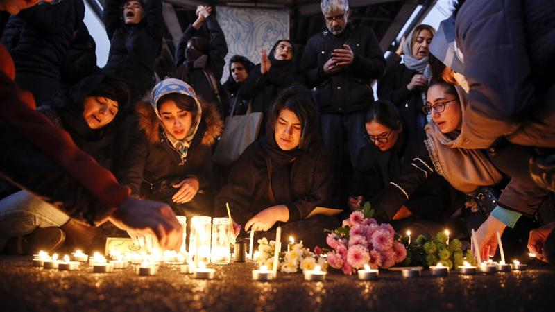 Iranians light candles for victims of Ukraine International Airlines Boeing 737-800 during as they protest in front of the Amir Kabir University in Tehran [Abedin Taherkenareh/EPA]