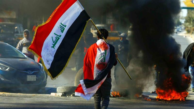 A demonstrator carries an Iraqi flag as he walks near burning tires, during ongoing anti-government protests in Najaf, Iraq January 12, 2020. REUTERS/Alaa al-Marjani [Daylife]