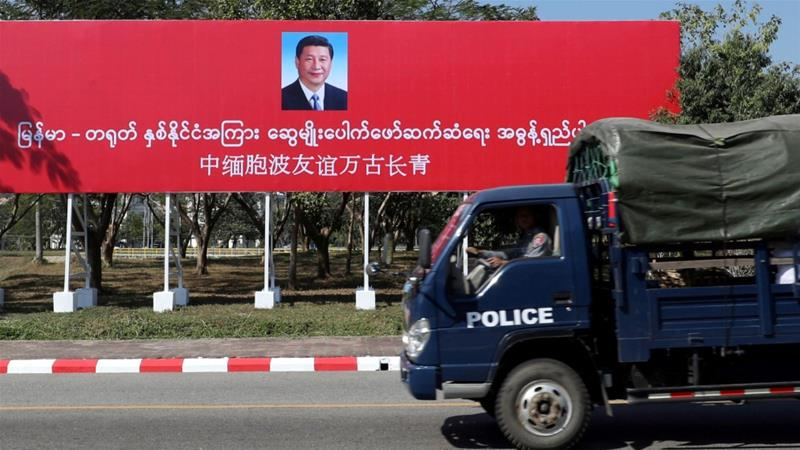 A police van in Naypyitaw drives by a banner welcoming Chinese President Xi Jinping ahead of his visit to Myanmar [Ann Wang/Reuters]