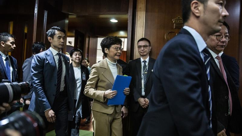 Lam (centre) leaves the Hong Kong legislature after her question-and-answer session for 2020 [Isaac Lawrence/AFP]