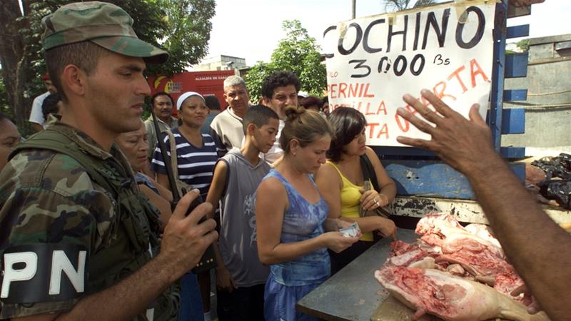 Nicolas Maduro's administration started giving away holiday pork about three years ago as part of a promise to deal with chronic hunger and undernourishment [File: Jorge Silva/Reuters]
