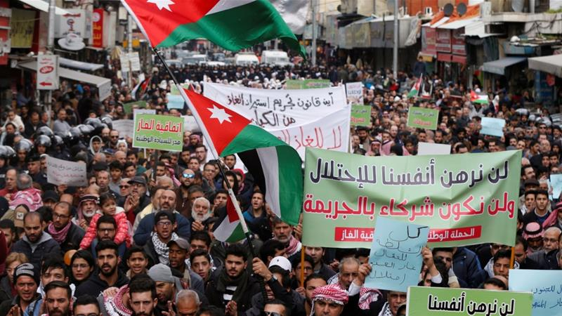 Demonstrators hold Jordanian flags during a protest against the deal to import natural gas from Israel [Muhammad Hamed/Reuters]