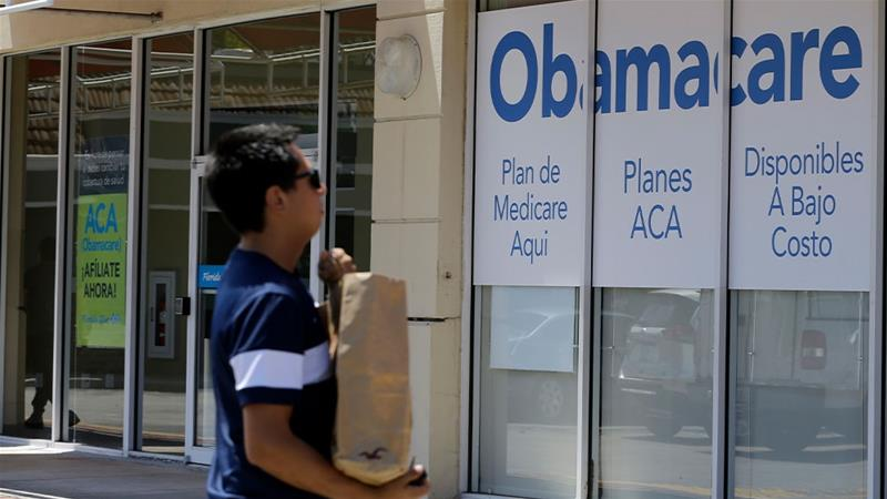 A man walking by a healthcare insurance office in Hialeah, Florida [Alan Diaz/AP photo]