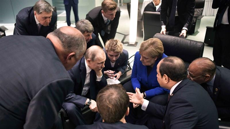 Russian President Vladimir Putin, German Chancellor Angela Merkel and other officials talk during a conference on Libya at the German Chancellery in Berlin on January 19, 2020 [AP]