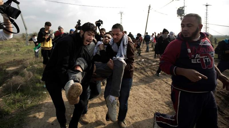 Majed is rushed away by friends after being shot in the leg by an Israeli soldier [Yaser Murtaja/Al Jazeera]