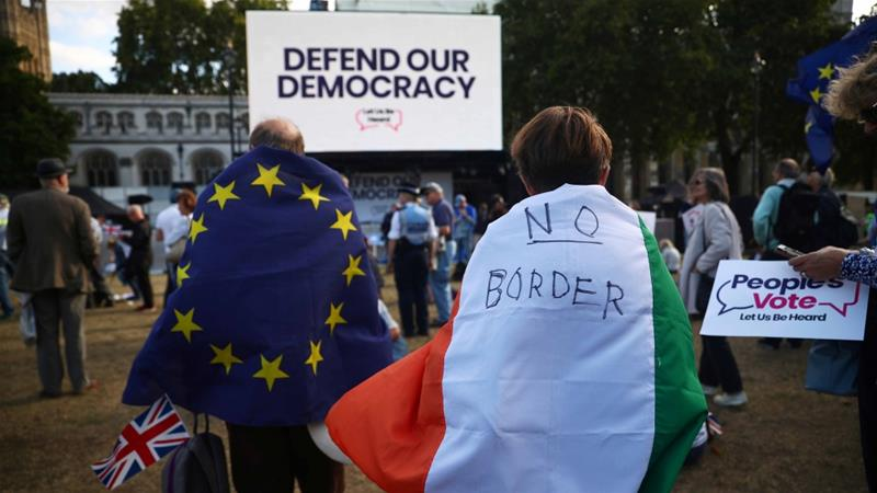 A woman wearing an Irish flag and a man wearing an EU flag demonstrate in front of the parliament at Westminster, in London on September 4, 2019 [Reuters/Hannah McKay]