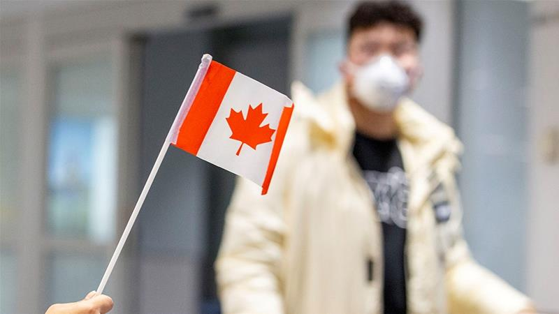 A traveller wears a mask at Pearson airport arrivals, shortly after Toronto Public Health received notification of Canada's first presumptive confirmed case of novel coronavirus, in Toronto, Ontario [Carlos Osorio/Reuters]