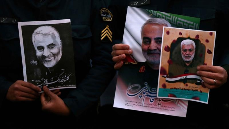 Iranian guards hold a picture of Iranian General Qassem Soleimani, during a protest against his killing, in front of the UN office in Tehran, on  January 3, 2020 [WANA/Nazanin Tabatabaee via Reuters]
