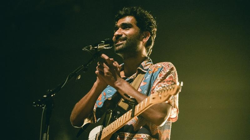 In a handout photograph taken in December 2019, singer Prateek Kuhad reacts as he performs on stage in New Delhi [Prashin Jagger/AFP]