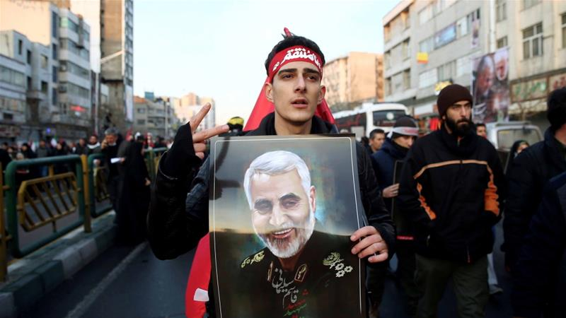An Iranian man holds a picture of General Qassem Soleimani during his funeral procession in Tehran on January 6, 2020 [Nazanin Tabatabaee/WANA via Reuters]