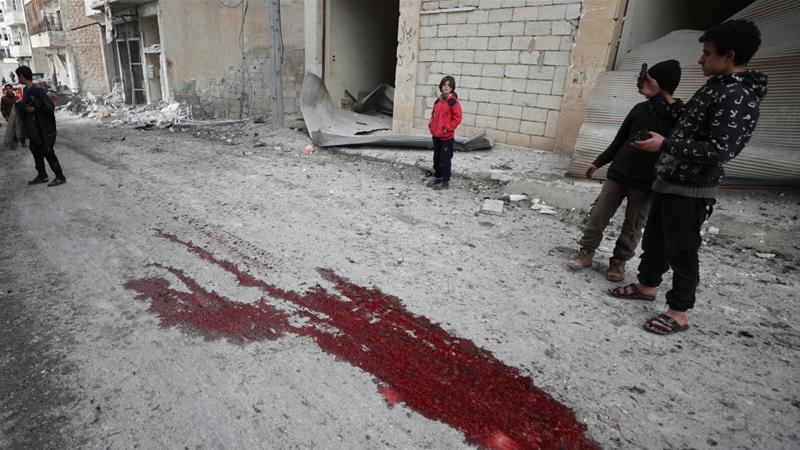 Syrian children gaze at a pool of blood following a reported government air raid in the town of Ariha in the Idlib province on January 5, 2020, killing at least nine civilians [Omar Haj Kadour/AFP]