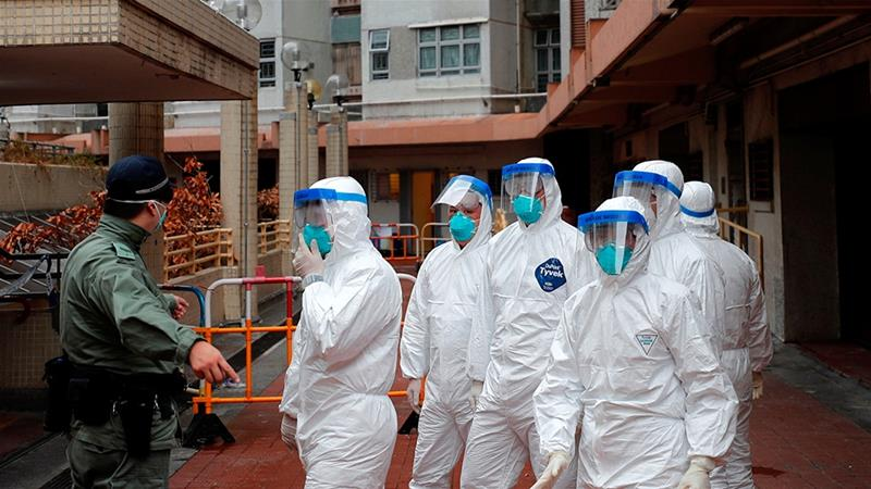 Police in protective gear wait to evacuate residents from a public housing building following the outbreak of the novel coronavirus in Hong Kong China