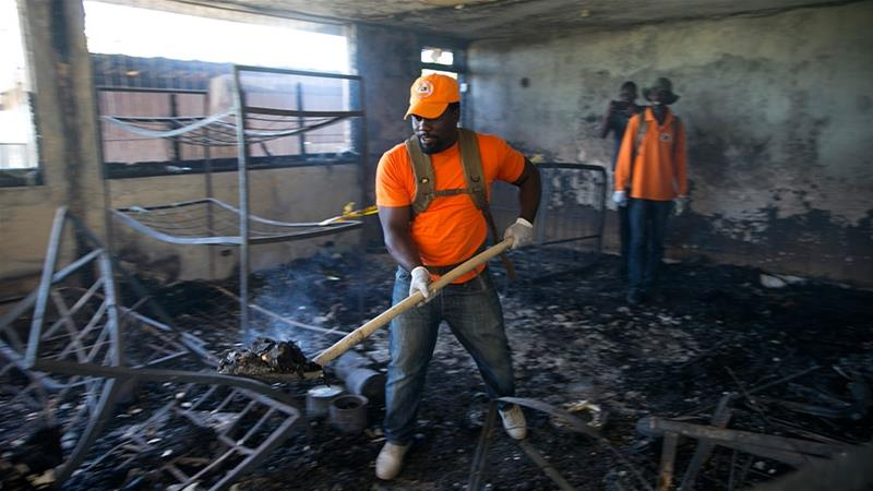 A civil protection worker shovels charred debris from inside the Orphanage of the Church of Bible Understanding where a fire broke out, killing 13 children in Kenscoff, on the outskirts of Port-au-Prince, Haiti [Dieu Nalio Chery/AP Photo]