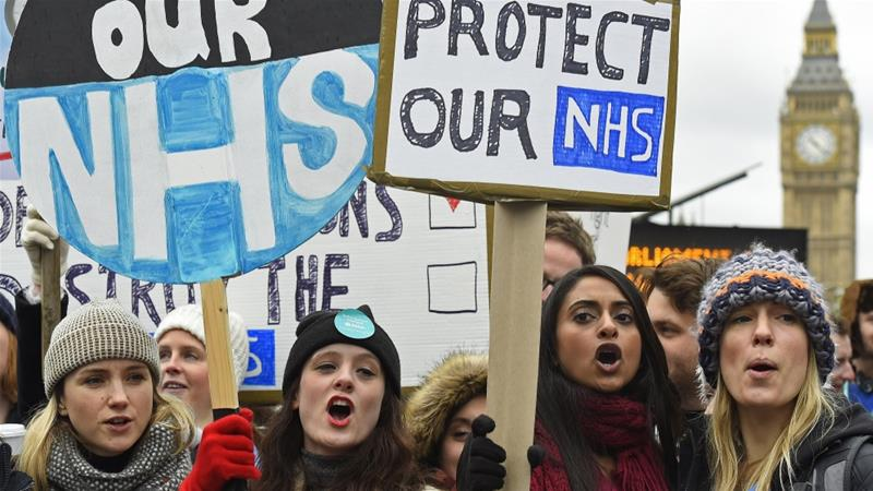 Junior doctors and NHS staff hold placards during a strike outside St Thomas' Hospital in London, UK [File: Toby Melville/Reuters]