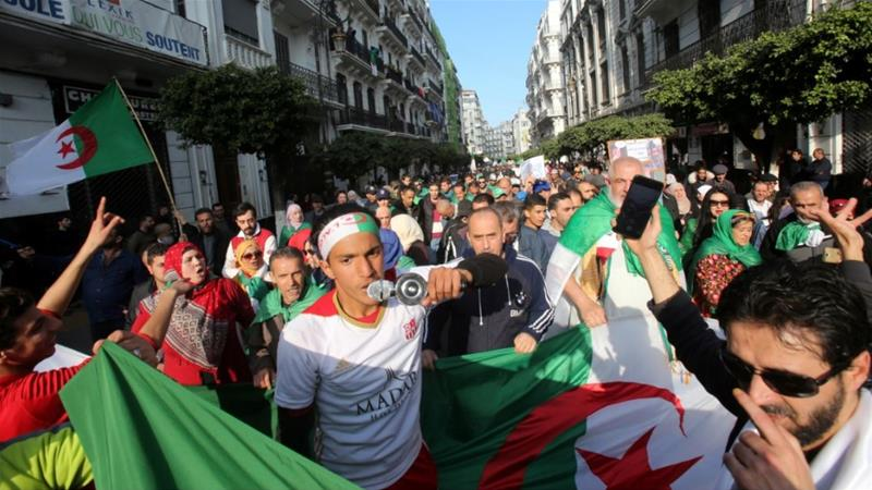 Demonstrators carry national flags as they march in Algiers [Ramzi Boudina/Reuters]