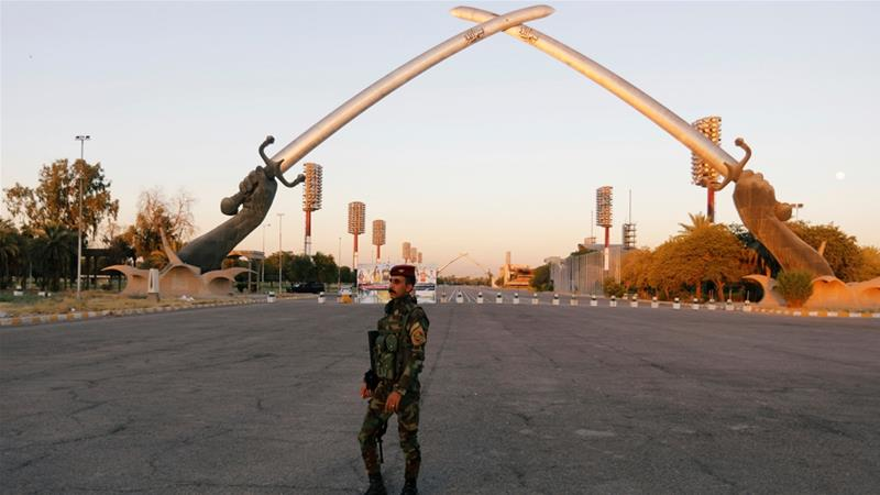 An Iraqi security officer walks near the 'Arch of Victory' memorial in the Green Zone [File: Khalid Al-Mousily/Reuters]