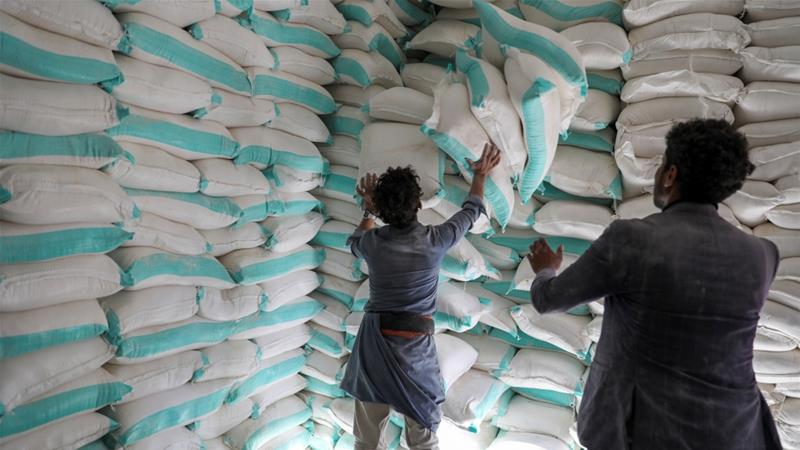 Workers handle sacks of flour at a WFP food aid distribution centre in Yemen's capital Sanaa [File: Khaled Abdullah/Reuters]