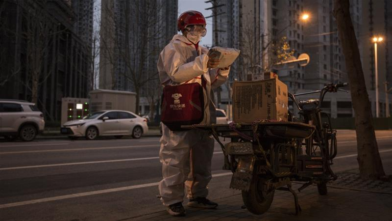 An expressman wears a protective mask and suit as he delivers packages on a bicycle on February 1, 2020 in Wuhan, Hubei province, China [Stringer/Getty Images/Reuters]