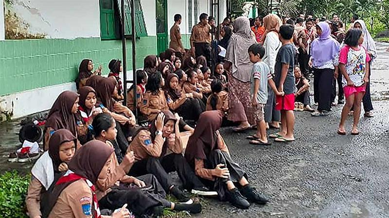 School students huddle together following their rescue in Yogyakarta, after a flash flood killed several students [BNPB/AFP]